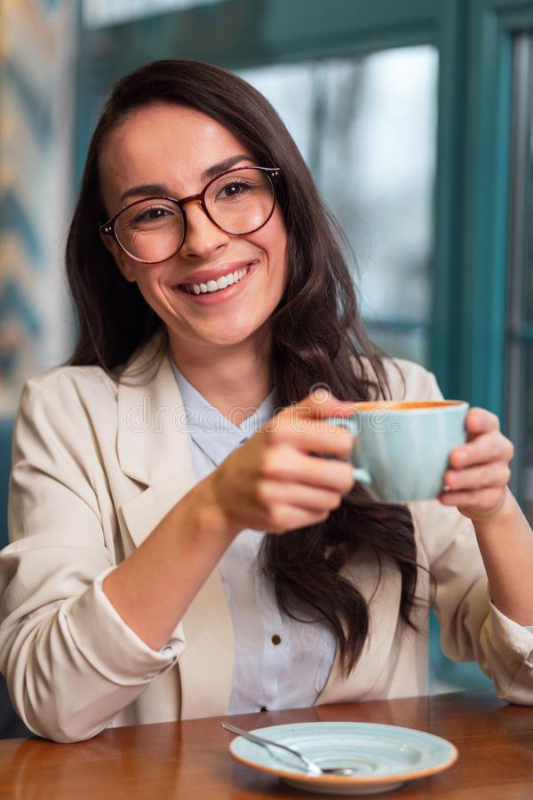 Pensive jolly woman deriving pleasure from coffee royalty free stock photo