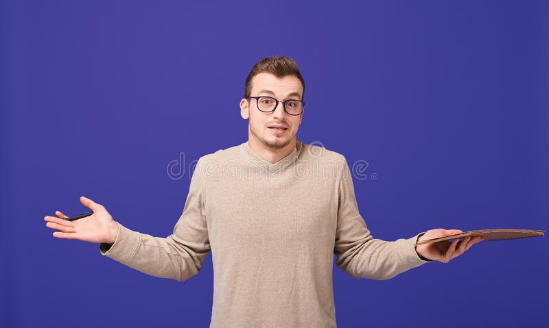 Pensive journalist with draft notebook in sweater and glasses spread arms to sides and shrugsshoulders stock image