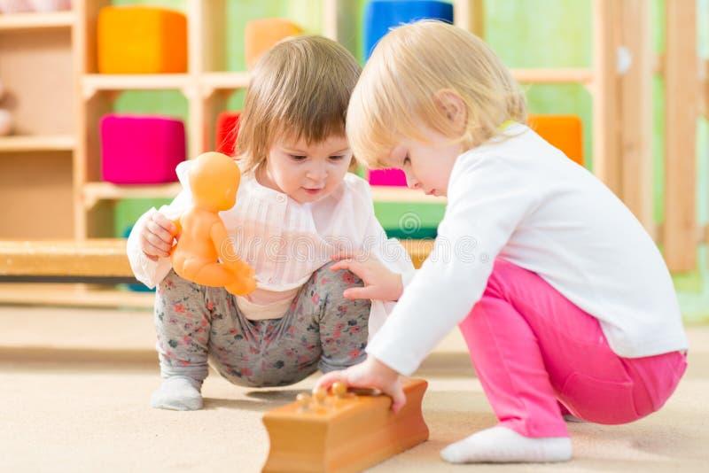 Pensive kids playing in kindergarten room royalty free stock photo