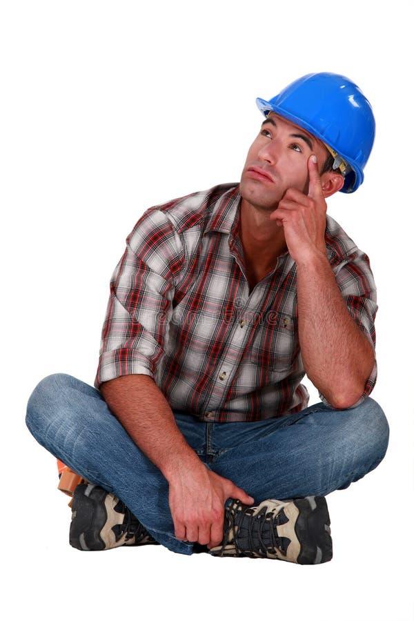 Pensive laborer sitting