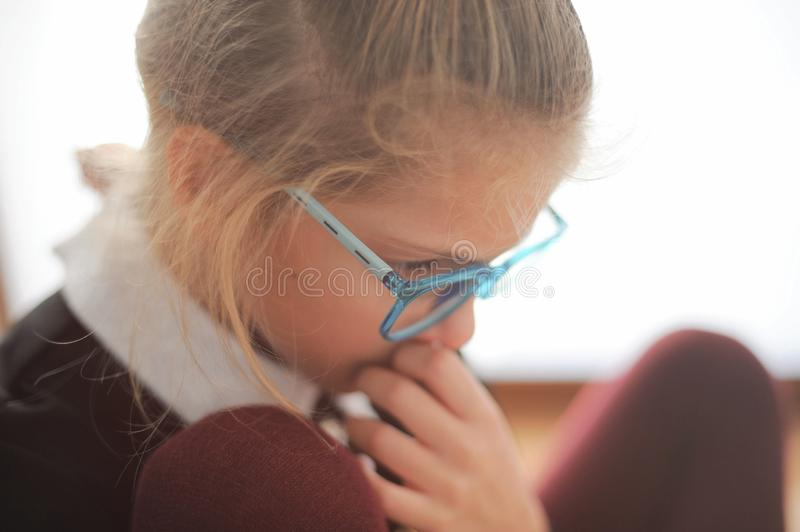 Pensive little beautiful girl in glasses and school uniform thin royalty free stock photos