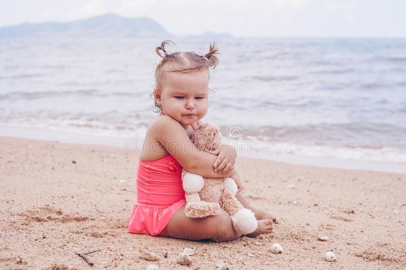 Pensive little girl hugging teddy bear and looking away while sitting on seashore. Pensive little girl hugging teddy bear and looking away while sitting on royalty free stock photo