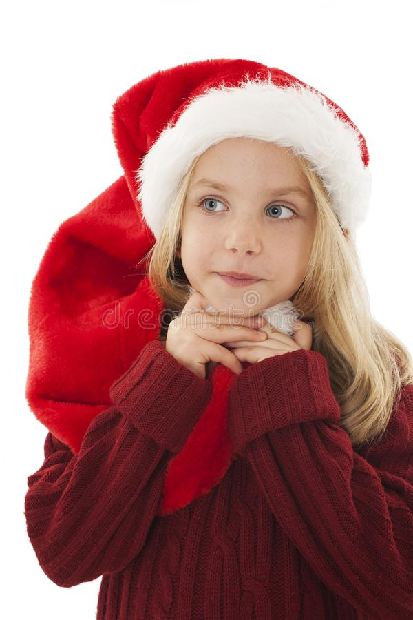 Pensive little girl in red Santa hat. royalty free stock images