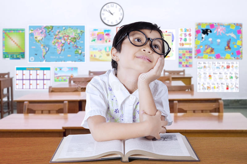 Pensive little learner thinking idea in the class. Portrait of attractive elementary school student back to school and sitting in the class while thinking idea royalty free stock images