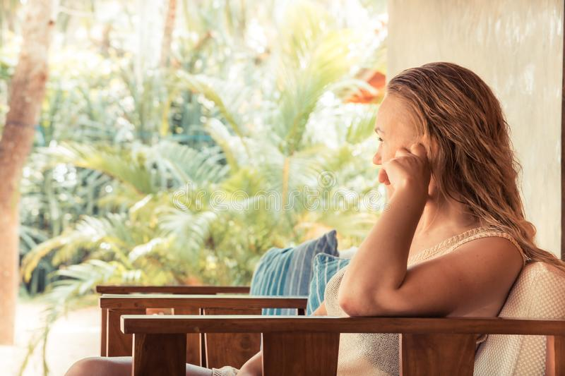 Pensive lonely beautiful tanned woman wet hair relaxing outdoors in chair and looking away during tropical summer beach holidays royalty free stock images