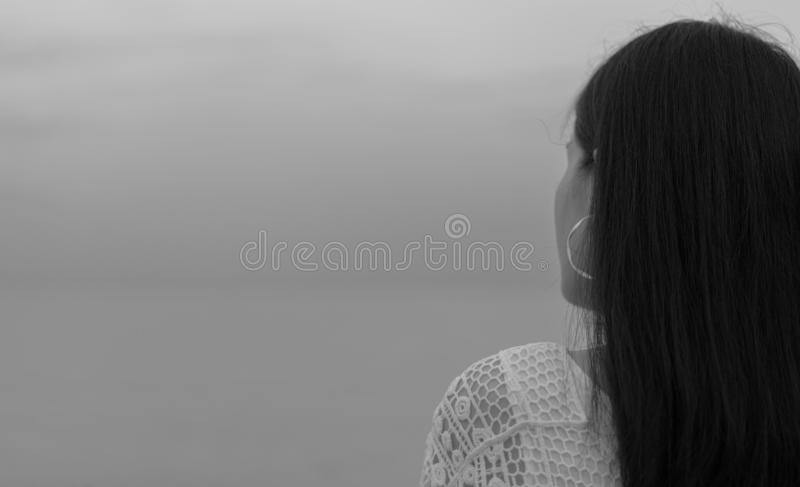 Pensive lonely young Asian woman. Back view of woman with sad feeling in black and white scene at the sea. Depressed and stressed stock photography