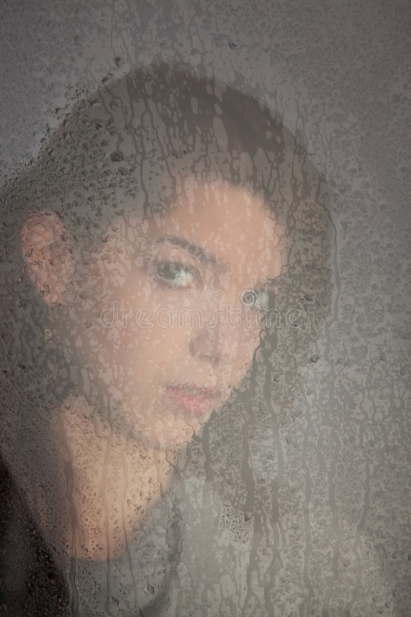 Pensive lonely young girl at the window royalty free stock photo