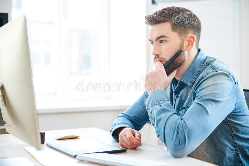 Pensive male designer thinking and making blueprints using pen tablet stock photos