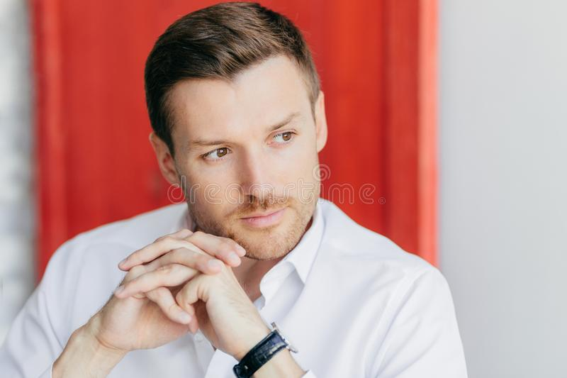 Pensive male director keeps hands presssed together, looks thoughtfully aside, being deep in thoughts before important meeting, po. Ses indoor against red and stock images