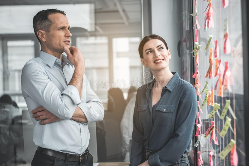 Glad colleagues watching at colorful stickers stock photos