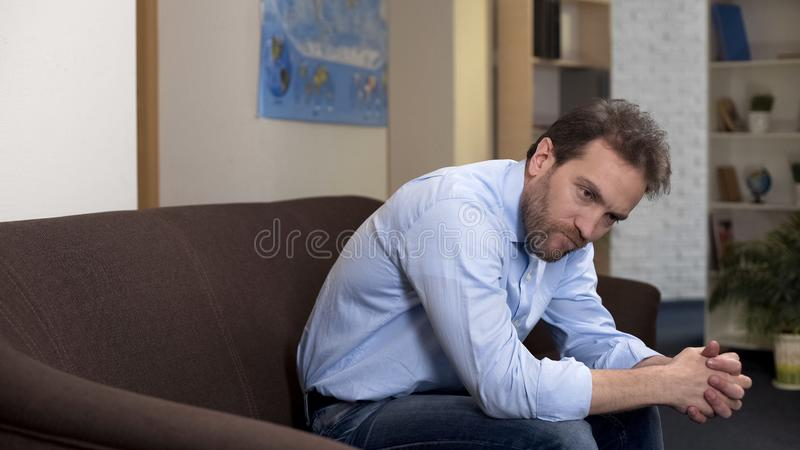 Pensive male sitting on couch alone at home, losing job, unemployment problem royalty free stock images