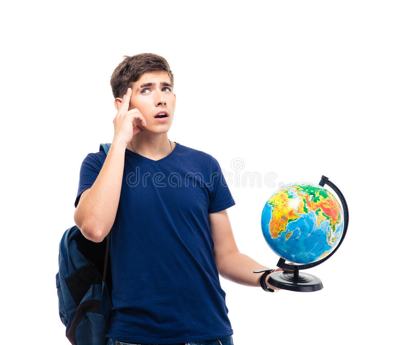 Pensive male student holding globe. And looking up at copyspace isolated on a white background royalty free stock photo