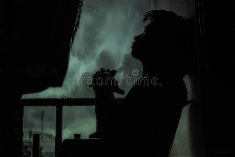 Pensive man on balcony in rain stock images