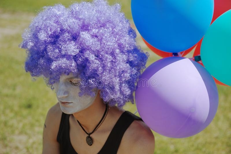 Pensive man in the clown costume next to the balloons stock image