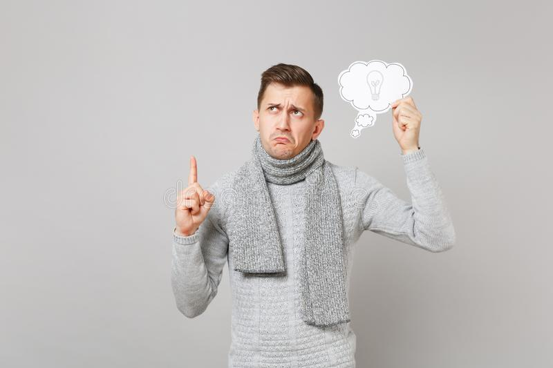 Pensive man in gray sweater, scarf holding say cloud with lightbulb, index finger up with great new idea on stock image