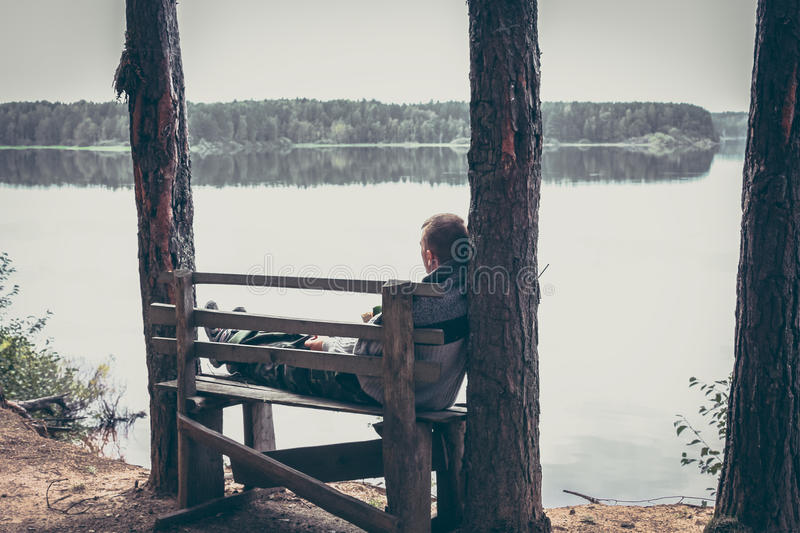 Pensive man on the high edge of river bank sitting on the bench and looking on beautiful scenery with tranquil water stock image