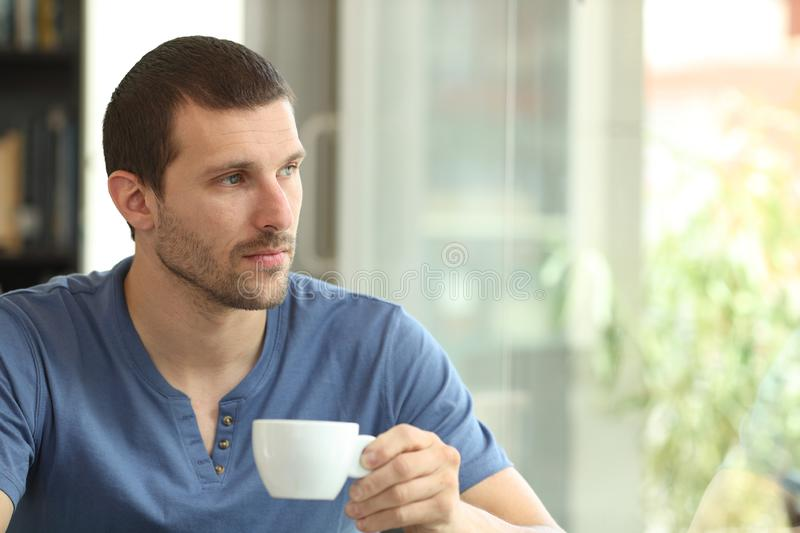 Pensive man holding coffee cup looks away through a window. In a bar or home royalty free stock photography