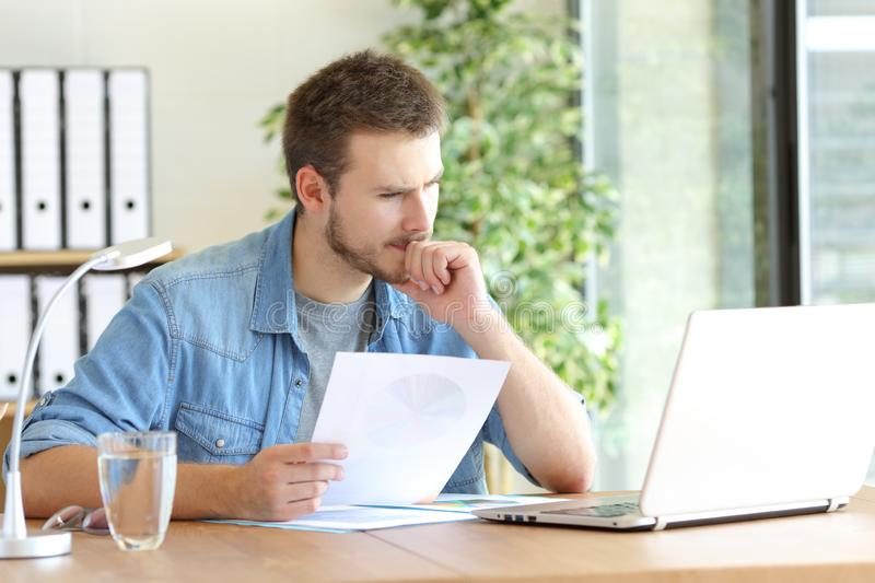 Pensive man holding document reading laptop content royalty free stock images