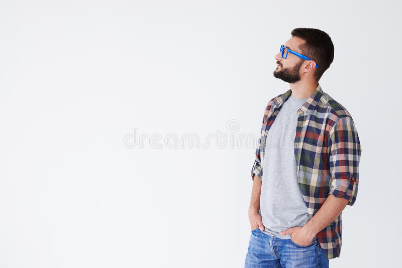 Pensive man holding hands in pockets looking at copy space royalty free stock photo