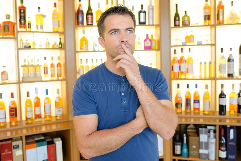 Pensive man in liquor store stock photography