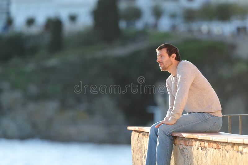 Pensive man looking away sitting in a balcony royalty free stock images