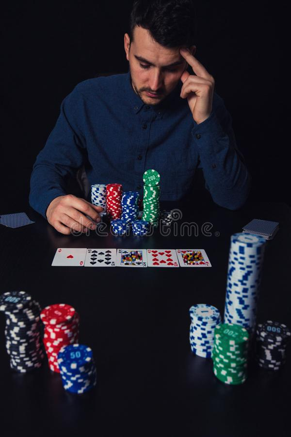Pensive man poker player seated at the casino table, keeps hand to forehead, thinking as looks as playing cards and his chips bank stock photos