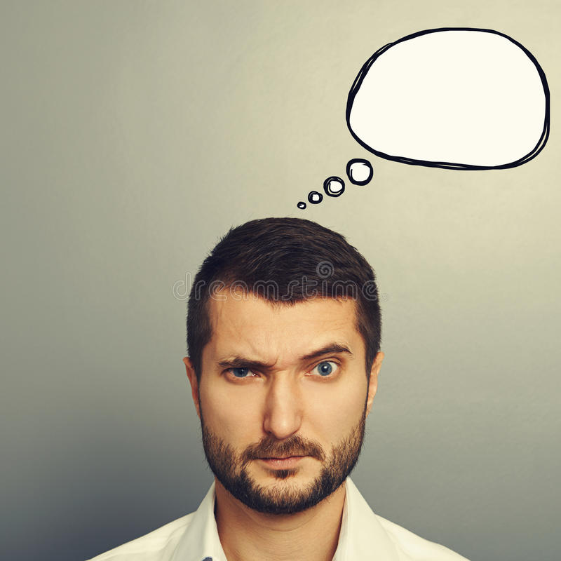 Pensive man with speech bubble. Pensive man with empty speech bubble looking at camera over grey background royalty free stock images