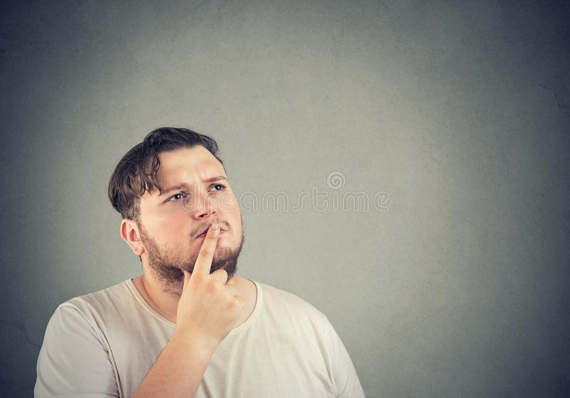 Pensive man touching lips while remembering royalty free stock photos