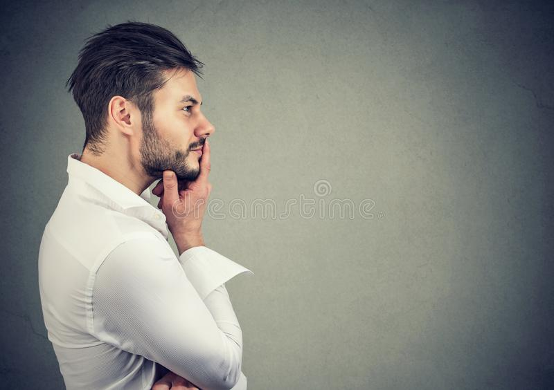 Pensive man touching lips while remembering stock images