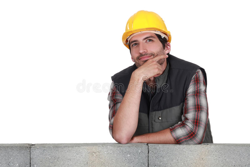 A pensive mason. Leanin gon a wall stock images