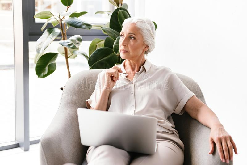 Pensive mature business woman working on laptop stock photography