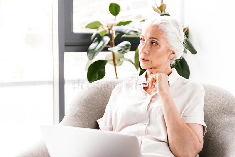 Pensive mature business woman working royalty free stock photo