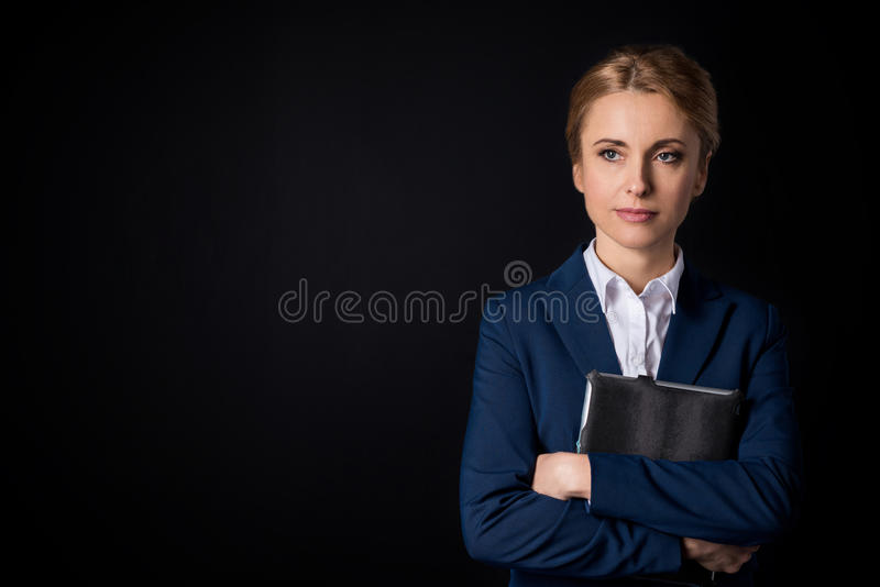 Pensive middle aged businesswoman holding digital tablet and looking away stock photo