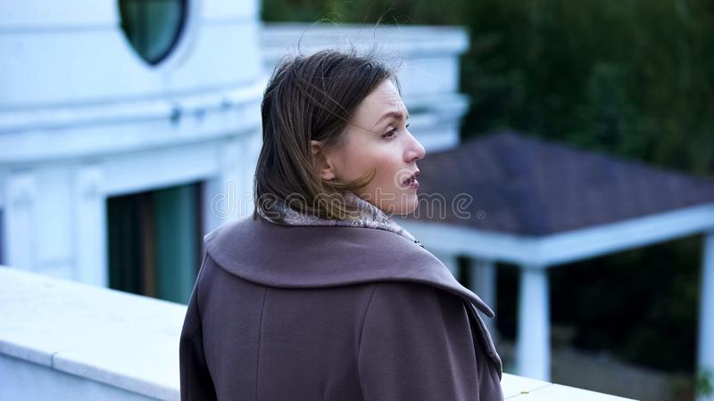 Pensive middle-aged woman standing on balcony of estate, feeling sad and lonely stock photos
