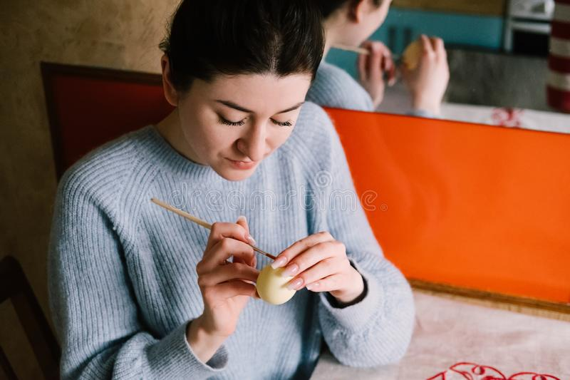 Pensive millennial girl painting Easter egg at homeapril,art,arts and culture,blue,body part,brush,caucasian,color,craft,creative, stock photo