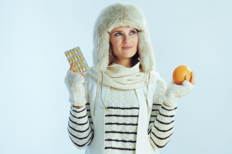 Pensive modern woman with orange and blister pack of vitamins royalty free stock photography