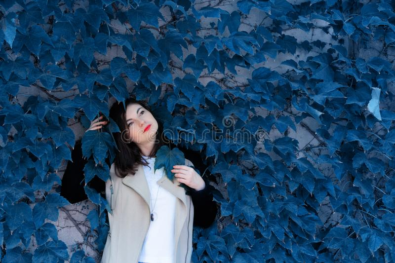 Pensive and moody young girl standing against a wall with ivy. Foliage tinted in color of the year 2020 - Classic Blue. Place for text. Harmony with nature royalty free stock image