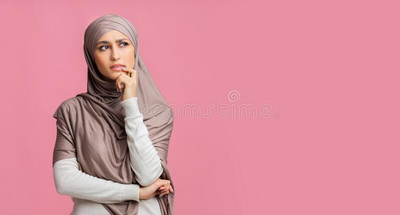Pensive muslim girl thinking and looking away on pink studio background royalty free stock photos