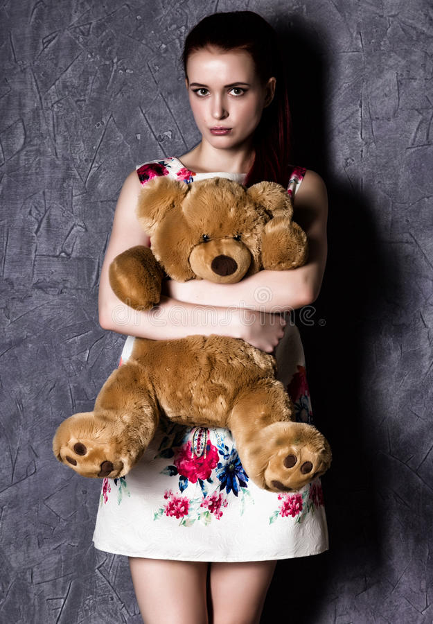 Pensive or offended beautiful woman embraces a teddy bear on a gray background. stock image