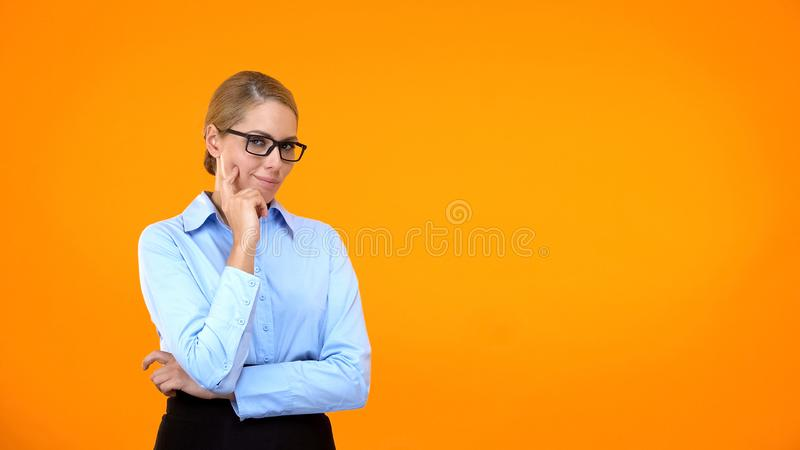 Pensive office worker looking camera on orange background, choice hesitation royalty free stock image