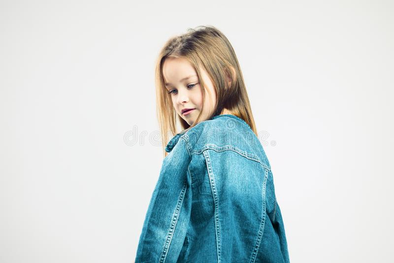 Pensive portrait of a child. little girl in denim jacket posing in the studio. kids fashion. Gray background. portrait stock images
