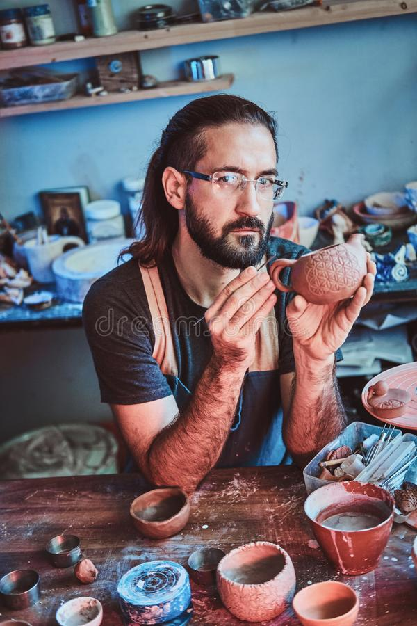Pensive potter in glasses at his own workshop is workig on a new handmade teapot. Pensive entusiastici potter in glasses at his  own workshop is workig on a new royalty free stock photos