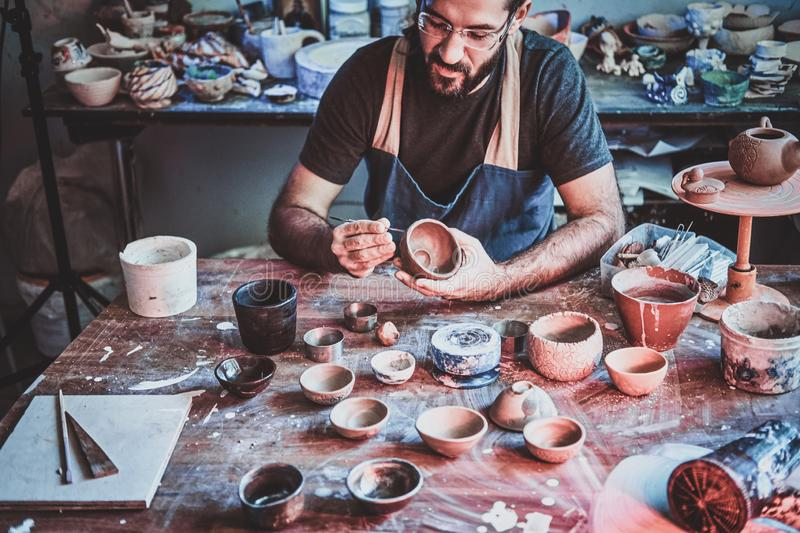 Pensive potter in glasses at his own workshop is workig on a new handmade teapot. Pensive entusiastici potter in glasses at his  own workshop is workig on a new stock photos