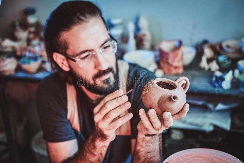 Pensive potter in glasses at his own workshop is workig on a new handmade teapot. Pensive progressive potter in glasses at his  own workshop is workig on a new stock image