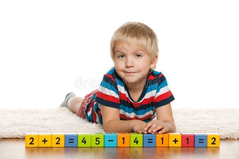 Pensive preschool boy with blocks stock photography