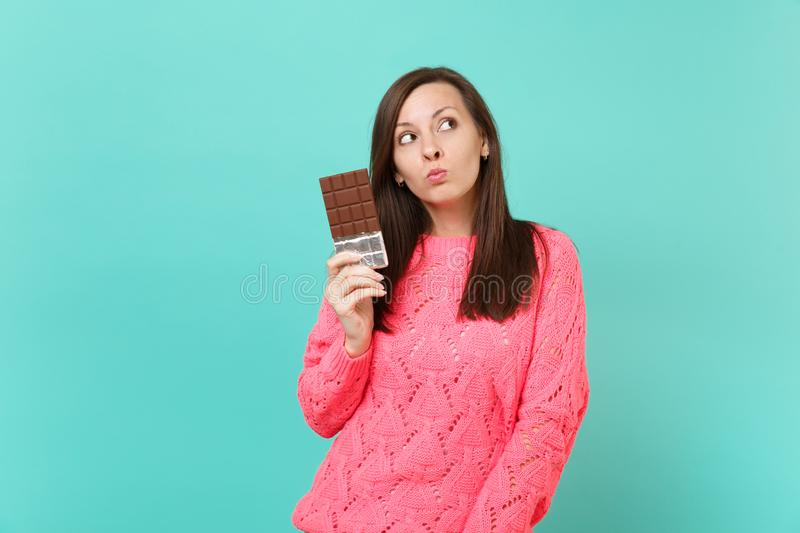 Pensive pretty young woman in knitted pink sweater holding in hand chocolate bar, looking up isolated on blue turquoise royalty free stock photos