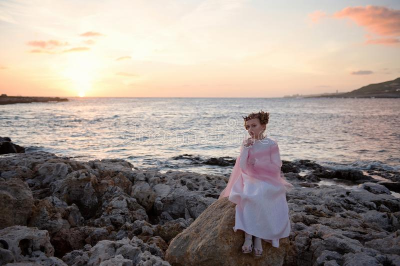 Pensive sad princess girl in a pink dress and a diadem is sitting on a rock on the ocean seashore and meets the dawn of the sunris royalty free stock photos