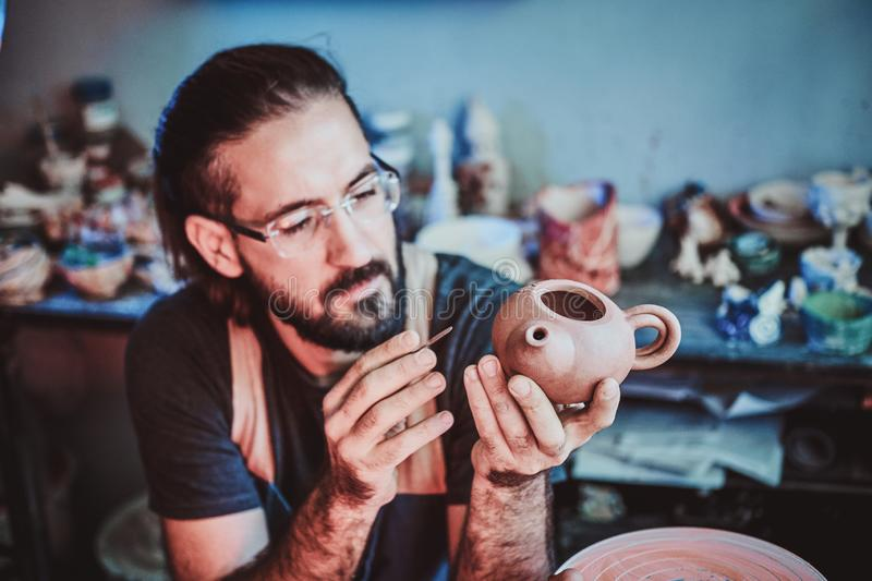 Pensive potter in glasses at his own workshop is workig on a new handmade teapot. Pensive progressive potter in glasses at his  own workshop is workig on a new stock images