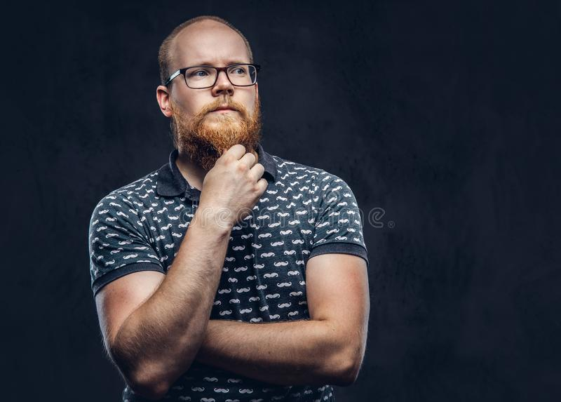 Pensive redhead bearded male in glasses dressed in a t-shirt posing with a hand on chin. Isolated on dark textured. Pensive redhead bearded male in glasses royalty free stock image