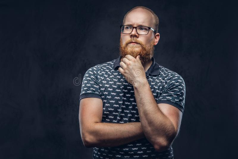 Pensive redhead bearded male in glasses dressed in a t-shirt posing with a hand on chin. Isolated on dark textured. Pensive redhead bearded male in glasses royalty free stock photos
